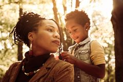African American woman with daughter in park. Daughter making mom`s hairstyle in the park. African American women with daughter in park stock images