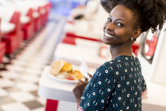 African american woman in diner. Young african american woman eating in the diner Stock Image
