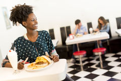 African american woman in diner. Young african american women eating in the diner Stock Image