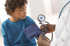 African American woman doctor taking a child's blood pressure. Royalty Free Stock Images