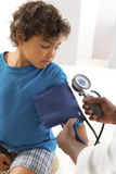 African American woman doctor taking a child's blood pressure. Stock Image