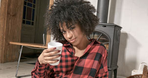 African american woman drinking coffee at home. Young african american woman drinking coffee at home, sitting on the floor. Girl with afro hairstyle Royalty Free Stock Photo