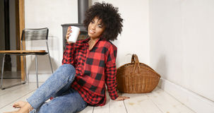African american woman drinking coffee at home. Young african american woman drinking coffee at home, sitting on the floor. Girl with afro hairstyle Stock Images