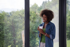 African American woman drinking coffee looking out the window. Beautiful young african american woman drinking coffee and looking through a window in her luxury Stock Photo