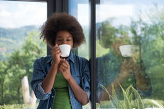 African American woman drinking coffee looking out the window stock photo