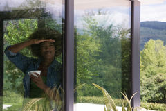 African American woman drinking coffee looking out the window. Beautiful young african american woman drinking coffee and looking through a window in her luxury Stock Images