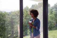African American woman drinking coffee looking out the window. Beautiful young african american woman drinking coffee and looking through a window in her luxury Royalty Free Stock Photos