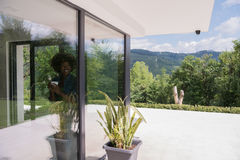 African American woman drinking coffee looking out the window. Beautiful young african american woman drinking coffee and looking through a window in her luxury Royalty Free Stock Photography