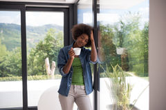 African American woman drinking coffee looking out the window. Beautiful young african american woman drinking coffee and looking through a window in her luxury Royalty Free Stock Images