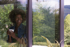 African American woman drinking coffee looking out the window. Beautiful young african american woman drinking coffee and looking through a window in her luxury Stock Photography