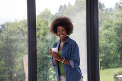 African American woman drinking coffee looking out the window. Beautiful young african american woman drinking coffee and looking through a window in her luxury Royalty Free Stock Image