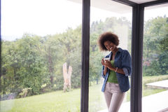 African American woman drinking coffee looking out the window. Beautiful young african american woman drinking coffee and looking through a window in her luxury Stock Photos