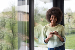 African American woman drinking coffee looking out the window. Beautiful young african american woman drinking coffee and looking through a window in her luxury Stock Image