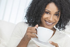 African American Woman Drinking Coffee or Tea. Beautiful smiling African American woman at home sitting on sofa or settee drinking cup of coffee or tea Royalty Free Stock Image