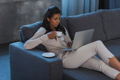 African american woman drinking coffee while using laptop at home. Young african american woman drinking coffee while using laptop at home Royalty Free Stock Photography