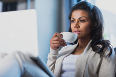 African american woman drinking coffee while using laptop at home. Young african american woman drinking coffee while using laptop at home Stock Images