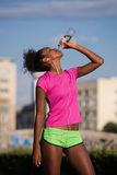 African american woman drinking water after jogging Stock Image