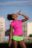 African american woman drinking water after jogging Royalty Free Stock Photos
