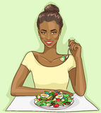 African American woman eating salad Stock Photos