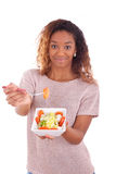 African American woman eating salad, isolated on white backgroun Royalty Free Stock Image