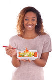 African American woman eating salad, isolated on white backgroun Stock Photos