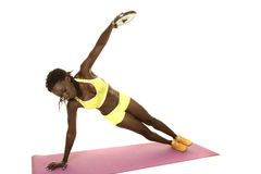 African American woman fitness green outfit side plank weight up. A woman doing a side plank with a weight Stock Photos