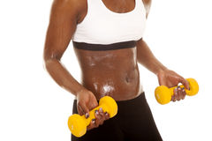 African American woman fitness white bra yellow weights body cur Stock Photo