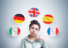 African American woman and five flags. Portrait of a pensive African American woman standing near a gray wall with and five national flags around her stock photos