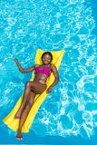 African american woman floating on inflatable mattress royalty free stock image