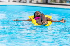 African american woman floating on inflatable mattress stock photos