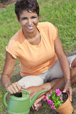 African American Woman Gardening Planting Flowers Stock Photo
