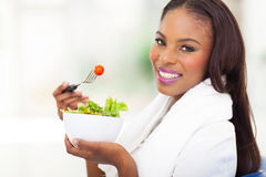 African american woman green salad. Attractive african american woman eating fresh green salad at home Royalty Free Stock Image