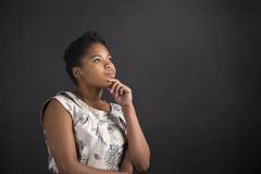African American woman with hand on chin thinking on blackboard background Stock Photography
