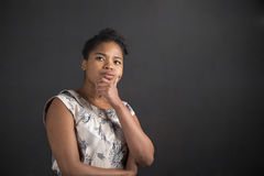 African American woman with hand on chin thinking on blackboard background Royalty Free Stock Images