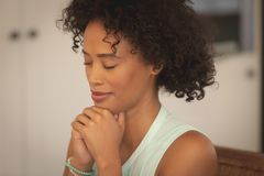 African American woman with hand clasped and eyes closed praying at dining table. Close-up of African American woman with hand clasped and eyes closed praying at royalty free stock images