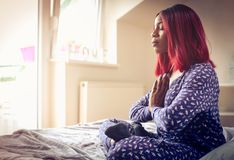 African American woman having meditation in bed at morning. royalty free stock photography