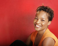 African-American Woman Headshot. An attractive, young African-American female model against a vibrant red background Stock Images