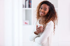 African American woman in her living room drinking holding a coffee tea mug - Black people royalty free stock images