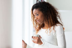 African American woman in her living room drinking holding a coffee tea mug - Black people royalty free stock photos