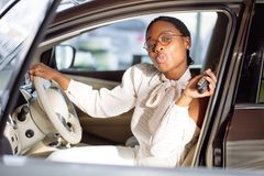 African woman with her new car showing key. African american woman with her new car showing key Stock Photo