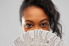 African american woman hiding face behind money. People, ethnicity and portrait concept - close up of african american young woman hiding her face behind fan of royalty free stock image