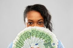 African american woman hiding face behind money. People, finances and wealth concept - close up of african american young woman hiding her face behind fan of royalty free stock photos