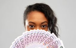African american woman hiding face behind money. People, finances and wealth concept - close up of african american young woman hiding her face behind fan of stock images