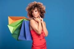 Afro girl enjoying shopping sales. African american woman holding colorful shopping bags, posing on blue background. Girl wearing red dress enjoying shopping Stock Photos
