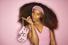African-American woman holding fuzzy dice. Portrait of smiling young African-American adult woman on pink background holding fuzzy dice Royalty Free Stock Photos