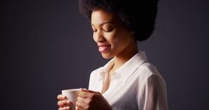 African American woman holding mug of hot tea and smiling. Looking down Stock Photo
