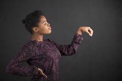 African American woman holding object out to side on blackboard background Royalty Free Stock Image