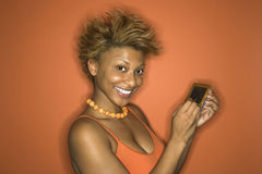 African-American woman holding pda. Portrait of smiling young African-American adult woman on orange background using her palmtop computer Stock Photography