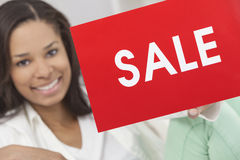 African American Woman Holding Sale Sign. Beautiful young African American woman smiling, relaxing and holding a red sale sign Royalty Free Stock Images