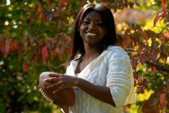 African-American woman holds football. African-American woman enjoying the fall outside with a football stock photo